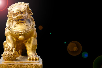 Chinese golden lion statue on dark background and flair effect
