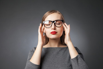 Woman in glasses with red lips meditating. eyes closed