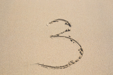 The numbers three written in the sand.