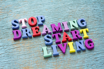 Stop dreaming start living phrase on vintage wooden background