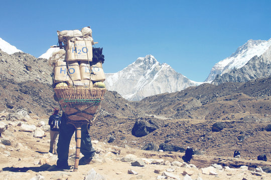Sherpa carrying a large load on his back