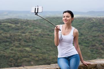 Junge hübsche Frau macht ein Selfie mit einem Selfie Stick während der Ferien und hat Spaß dabei