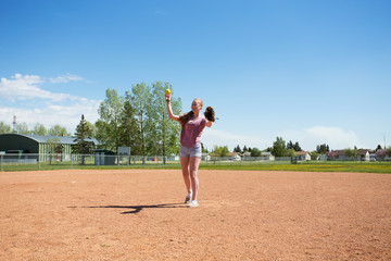 A laughing teenage girl in shorts and t shirt throwing a baseball at a baseball diamond in summer afternoon
