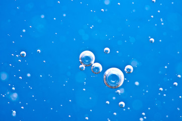 Close-up bubbles under water on blue background. Macro.