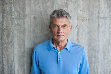 Portrait of senior man at concrete wall