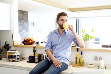 Man sitting in kitchen drinking coffee
