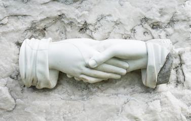 Hände aus Marmor auf einem Grabstein