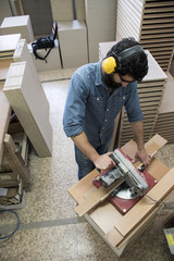 Carpenter with hearing protection and safety glasses using a circular saw