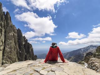 Spain, Sierra de Gredos, hiker sitting on rock in mountainscape