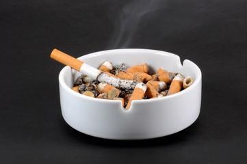 White ceramic ashtray full of smokes cigarettes. Selective focus.