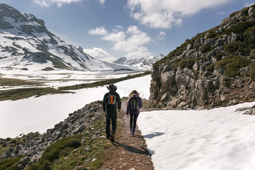Spain, Asturias, Somiedo, couple hiking in snowy mountains
