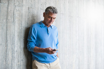 Senior man at concrete wall looking on cell phone