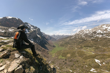 Spain, Asturias, Somiedo, man looking at the landscape sitting on mountaintop