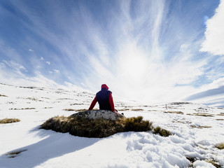 Spain, Sierra de Gredos, hiker sitting on rock in snow