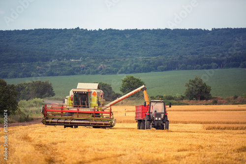 Wall mural Farming tractor plowing and spraying on field