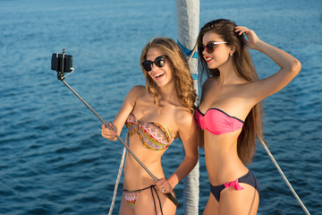 Cheerful girls with selfie stick. Women on yacht taking selfies. Young and attractive models. Photos from summer vacation.