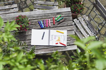 Drawing, sketch book with woman's drawing and coloring pencils on wooden garden table