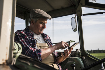 Farmer sitting in tractor using digital tablet