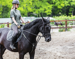 girl sportsman rides on horse
