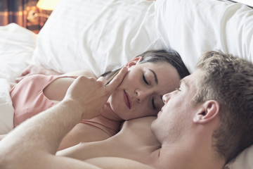 Young couple lying in bed cuddling