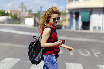 Italy, Verona, woman crossing street looking at cell phone