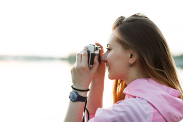 Young hipster girl takes pictures