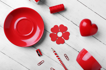 Red colour flat lay composition on white wooden background