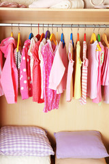 Girl's clothes on hangers in the wardrobe