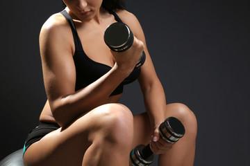 Female fitness model with dumbbells on dark grey background