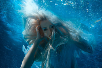 Woman with long blonde hair underwater.