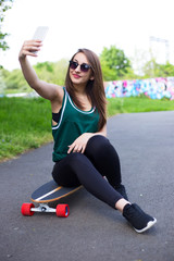 young woman in the park with her skateboard taking a selfie