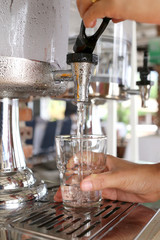 woman's hands were pressing cool water into drink glass.
