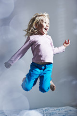 Girl jumping on bed