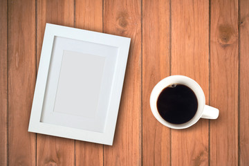 Photo frame with blank area and coffee cup on wood table
