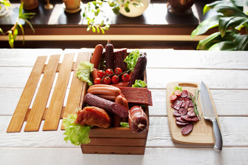 Sausage assortment in wooden box and sliced salami on cutting board with knife. Sausage variety on white wooden background.