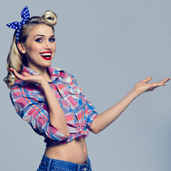 woman, dressed in pin-up style, showing something or copyspace