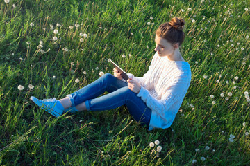 Girl sitting on the grass and looking at tablet computer