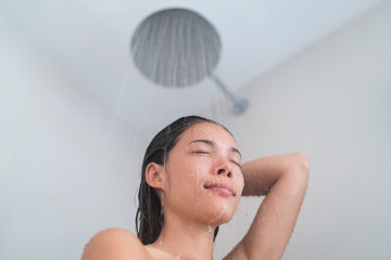 Young woman taking a hot shower showering hair relaxing under warm running water from modern rainfall shower head at home or hotel. Asian girl in luxury bathroom enjoying her bathtime.