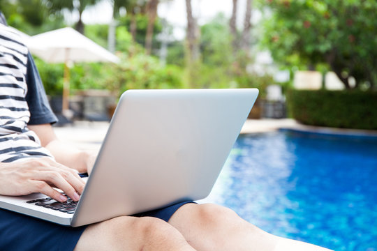 Man using a laptop in the pool on vacation - work anywhere and internet work concept