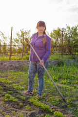 Smiling middle-aged woman leaning on her rake