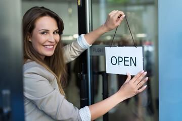 Woman hanging open sign on door  Fototapete