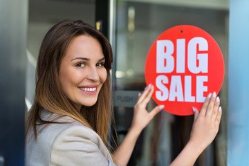 Woman with sale sign in clothes shop
