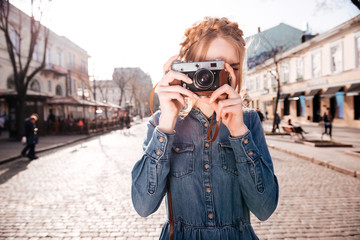Woman taking pictures with old vintage camera on the street
