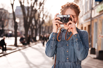 Concentrated woman taking pictures outdoors using old vintage camera