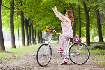 Beautiful girl on bike taking a selfie