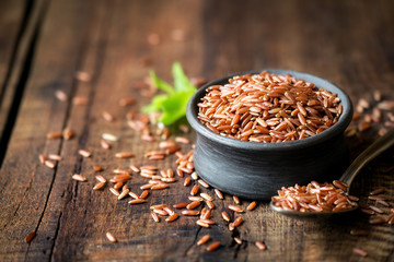 Red rice an a small ceramic bowl against dark rustic wooden background