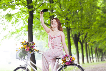 Beautiful girl on bike taking a selfie