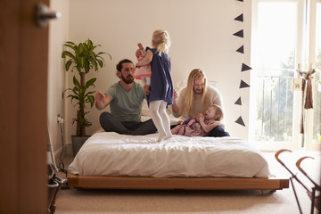 Parents Playing Game With Daughters In Bedroom
