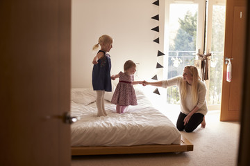 Mother Playing Game With Daughters In Bedroom