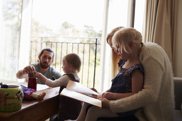 Family Drawing Pictures And Reading At Home Together